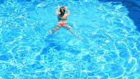 Blonde mooie vrouw die van het water in de pool genieten Mening van hierboven stock footage