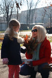 Blonde mother giving her blonde daughter an autumn leafs Stock Photo