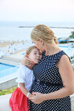 A blonde mother holding her beautiful daughter in her arm and kissing her head Royalty Free Stock Images