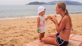 Blonde mother and little daughter sit on mat and eat roll stock video