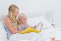 Blonde mother reading a story to her daughter Royalty Free Stock Photo