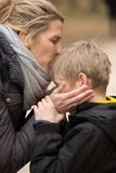 Blonde mother and son together, kiss, outdoors. Mother holds her son`s face in hands, and kisses his head outdoors in park Royalty Free Stock Image
