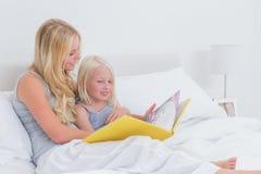 Blonde Mutter, die eine Geschichte zu ihrer Tochter liest Lizenzfreies Stockfoto