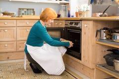 Blonde Mutter mit dem Schutzblech, das einen Kuchen in den Ofen einsetzt Stockfoto