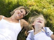 Blonde Mutter mit der Tochter, die Spaß auf Gras hat Lizenzfreies Stockbild