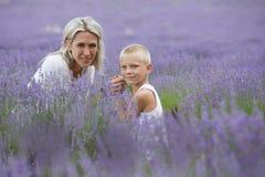 Blonde Mutter und ihr Sohn zusammen auf dem Lavendelgebiet Lizenzfreie Stockfotografie