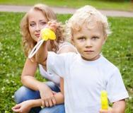Blonde Mutter und Sohn, die im Park spielt Stockbild