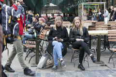 Blonde Mutter und Tochter betrachten das gleiche Sitzen dem Café auf Covent-Garten Lizenzfreie Stockfotografie