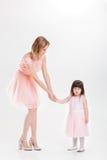 Blonde Mutter, welche die Hand der süßen kleinen Tochter im rosa dre hält Stockfoto
