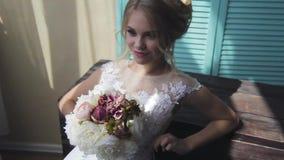 Blonde muy hermoso con los ojos azules en un vestido blanco de la novia cerca de una ventana con un ramo de flores metrajes