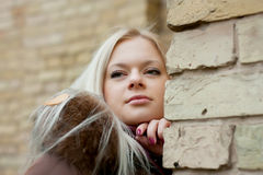 Blonde near the brick wall Royalty Free Stock Images