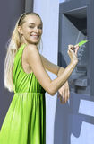 Blonde near a cash machine stock photos