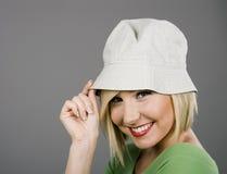 Blonde neigende Schutzkappe und Lächeln Lizenzfreies Stockbild