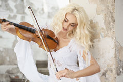 Blonde nette Frau, die Violine spielt Stockfotografie