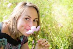 blonde nette junge Frau auf dem Gebiet mit Blumenrosasommer-Frühlingstag Stockfotografie