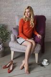 Blonde nette nehmen geeignete Geschäftsfrau im orange Strickjackenlächeln ab C Stockfoto
