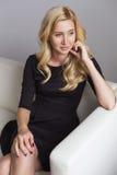 Blonde nette nehmen geeignete Geschäftsfrau im schwarzen Kleid ab, das auf a sitzt Stockbilder