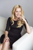 Blonde nette nehmen geeignete Geschäftsfrau im schwarzen Kleid ab, das auf a sitzt Lizenzfreie Stockfotografie