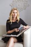 Blonde nette nehmen geeignete Geschäftsfrau im schwarzen Kleid ab, das auf a sitzt Stockfotografie