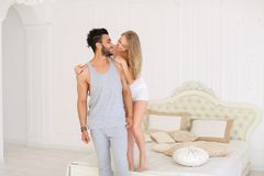 Blonde nice girl kissing hispanic man in badroom in morning. Blonde nice girl kissing hispanic men in badroom in morning. Concept of happy couple and resting on stock image