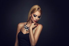 Blonde with nice makeup posing on a dark background Royalty Free Stock Images