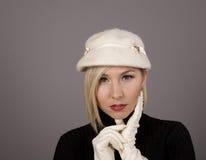 Blonde no chapéu forrado a pele com o polegar no lombo fotos de stock