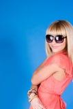 Blonde nos vidros um fundo azul em um vestido Imagens de Stock