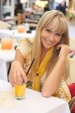 Blonde novo bonito com um vidro do suco Fotos de Stock Royalty Free