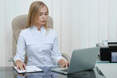 Blonde nurse sitting in hospital and working. stock image