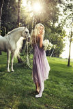 Blonde Nymphe mit Blumen und Pferd Stockbilder
