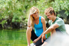 Blonde Paare sitzen in dem See zusammen Stockfoto