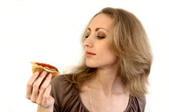 Blonde and pancake with caviar. The beautiful girl looks at a pancake with red caviar Royalty Free Stock Photos