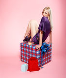 Blonde party girl. Full-length portrait of beautiful blonde party girl siiting on large birthday gift box on pink stock photo