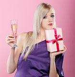 Blonde party girl. Portrait of beautiful blonde party girl looking upset with birthday gift box and glass of champagne on pink Stock Images