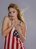 Blonde patriot. On a solid back ground a beautiful young blonde woman proudly shows her colors as she wears a flag tanktop and the wind whips her long blonde Royalty Free Stock Photo