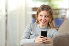 Blonde pensativo que usa un teléfono elegante en casa Imágenes de archivo libres de regalías