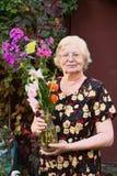 Blonde Pensionärschönheit mit Blumenblumenstraußabschluß oben Stockbild