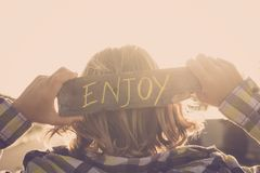 Blonde people young teenager with enjoy written on a natural piace of recycled wood. feeling and golden sunset atmosphere image. For positive life and vibes stock images