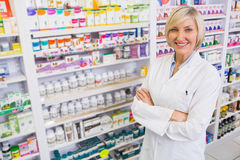 Blonde pharmacist with arms crossed smiling at camera Royalty Free Stock Photo