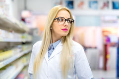Blonde pharmacist chemist woman standing in pharmacy drugstore, smiling and wearing glasses blonde pharmacist chemist woman stand Royalty Free Stock Photography