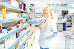 Blonde pharmacist selling antibiotics and prescription drugs. Pharmaceutical medical details royalty free stock image