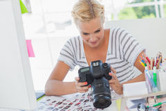 Blonde photo editor looking at a digital camera Stock Photography
