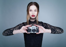 The blonde photographer. Studio photo blonde girl with a camera Royalty Free Stock Photos