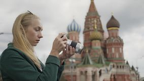 Blonde photographer taking pictures Saint Basil`s Cathedral, Moscow Russia. Side view of a blonde young tourist wearing a green coat making photos of Saint Basil stock video