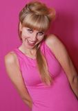 Blonde in pink dress. Bright sixties. Portrait of an extravagant blonde on  red background Royalty Free Stock Photography