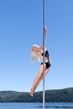 Blonde on pole performance of acrobatic program Royalty Free Stock Photos