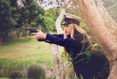 Blonde Polizistin, die mit Revolver zielt Lizenzfreie Stockbilder