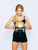 Blonde posing as american football girl on white background. Beautiful young woman wearing black outfit with American Stock Photo