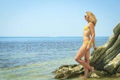 Blonde posing leaning against rock near ocean coast Royalty Free Stock Photos
