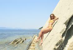 Blonde posing leaning against rock near ocean coast Stock Images